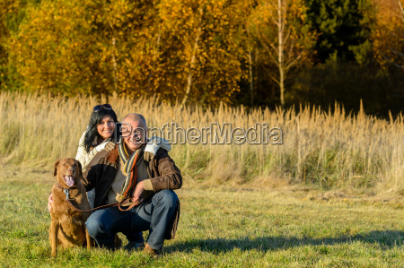 cheerful couple with dog in autumn