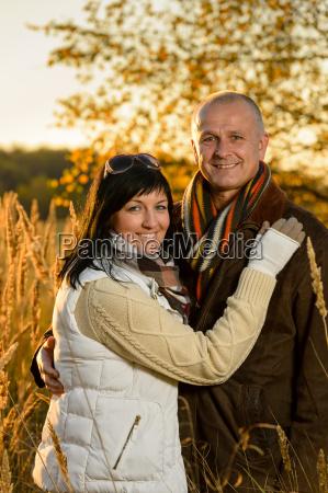 romantic couple hugging autumn sunset countryside