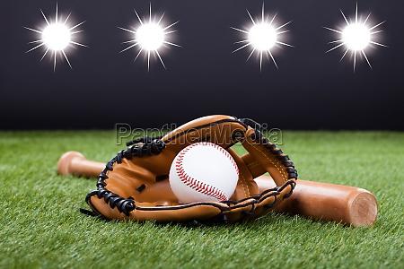 baseball glove with baseball and bat