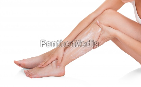 female applying moisturizer cream