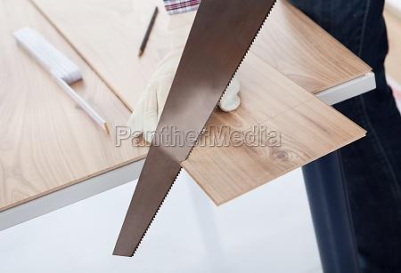 worker cutting piece of laminate
