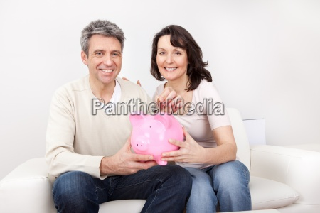 mature couple saving money in piggybank