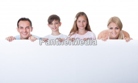 portrait of family behind blank board
