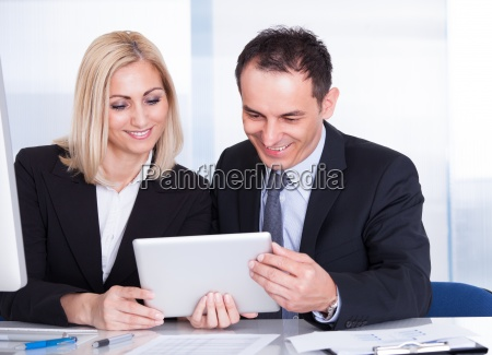 businessman and businesswoman looking at digital