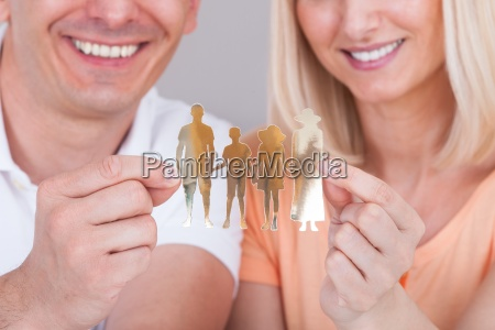 couple holding family figure cut out