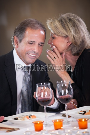 cheerful woman whispering in mans ear