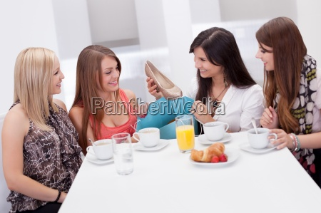 women discussing footwear together