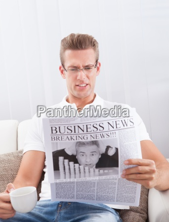 reading newspaper with the headline breaking