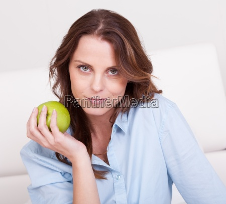 woman eating a healthy green apple