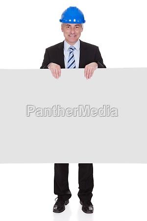mature male architect holding billboard
