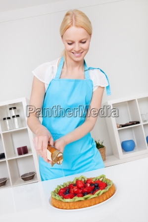 beautiful young woman making cake