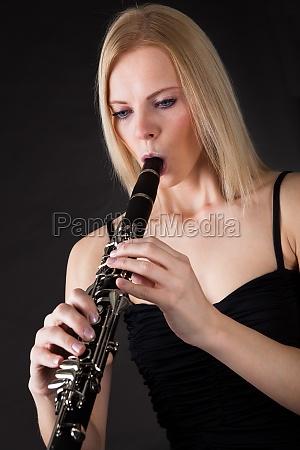 beautiful young woman playing clarinet