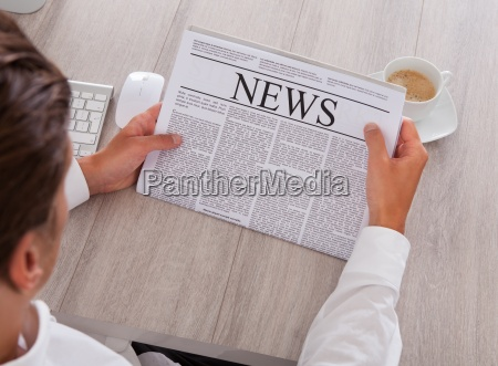man reading newspaper with coffee on