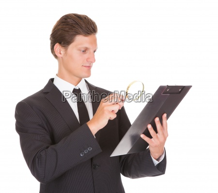 man looking through magnifying glass on