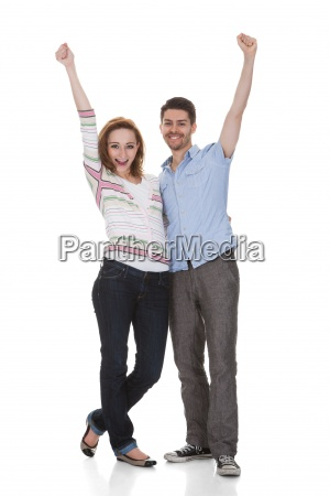 happy young couple raising hands