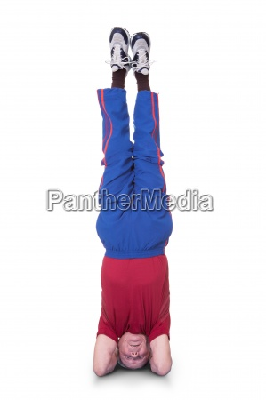 senior man performing yoga headstand