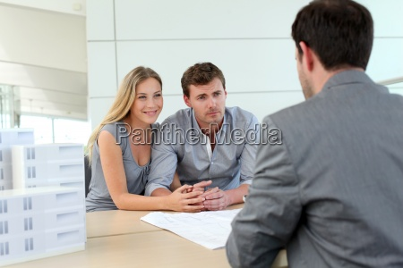 couple in real estate agency talking