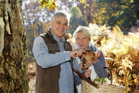 senior couple in forest holding ceps