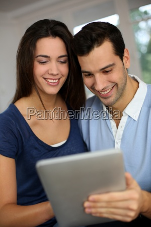 smiling couple websurfing on internet with
