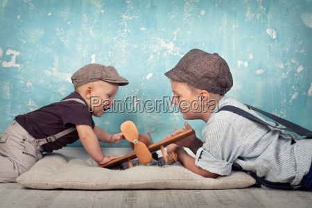 two brothers playing with wooden flyer