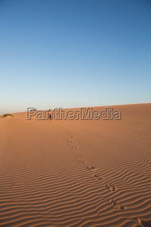 man walking in sand dunes in