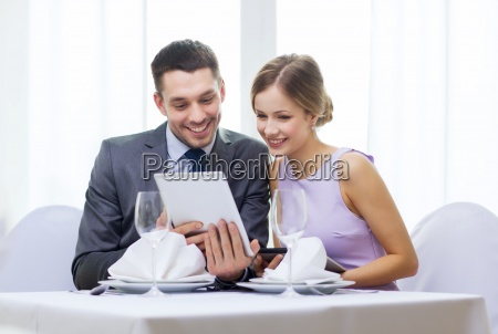 couple with menus on tablet pc