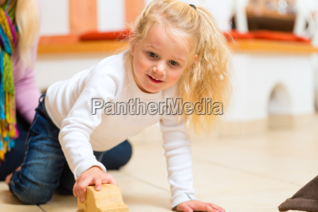 girl playing with wooden toy car