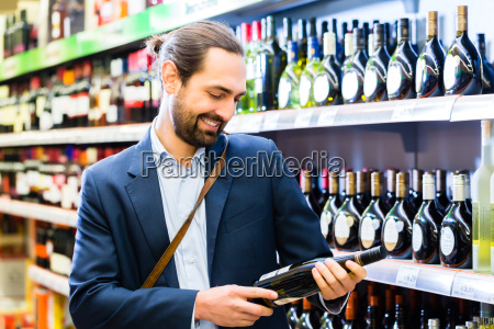 man chooses wine in a supermarket