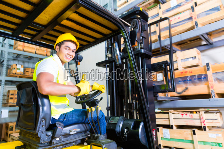 asian fork lift truck driver lifting