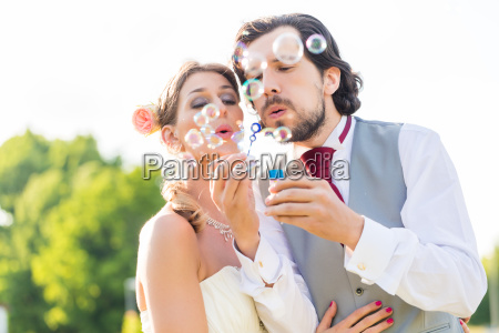 wedding couple blowing soap bubbles in
