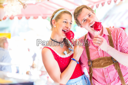 couple eating toffee apples at oktoberfest