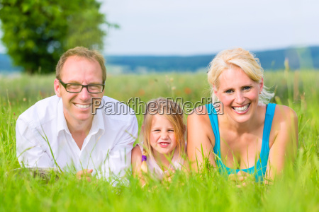 family lies in the grass on