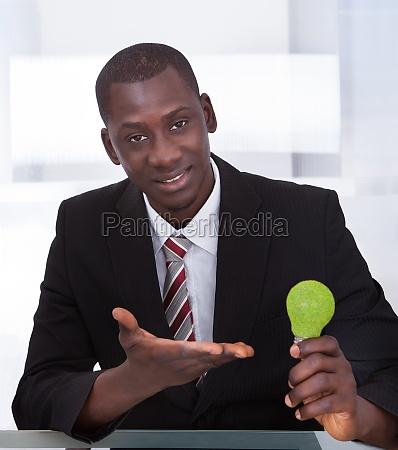 businessman holding ecological bulb
