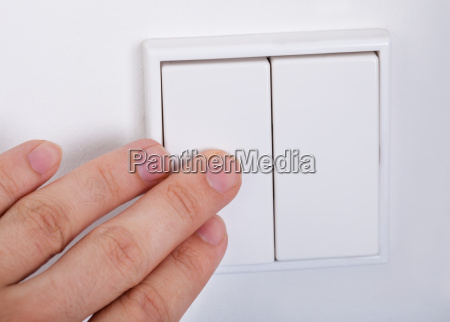 hand presses the light switch on