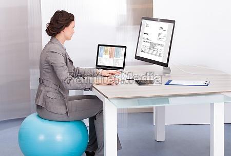 woman sitting on pilates ball using