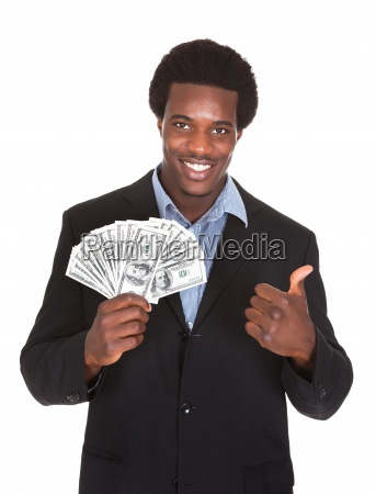 excited businessman holding dollar currency