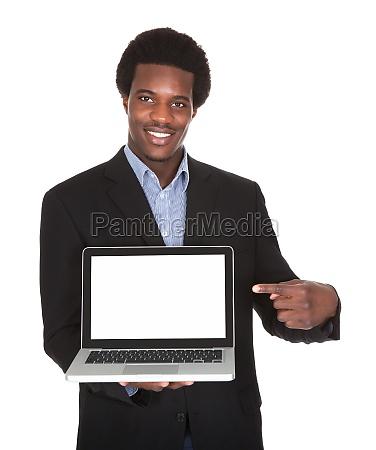 happy businessman holding laptop