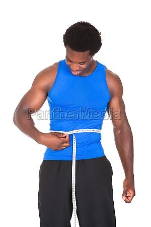 bodybuilder with a measuring tape around