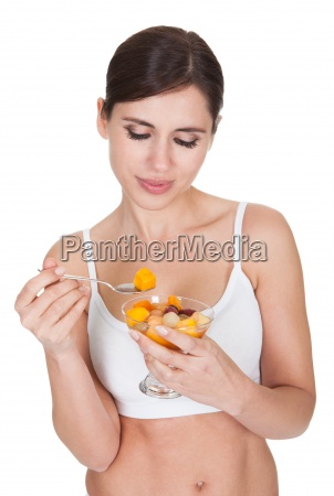 healthy woman eating fruit salad