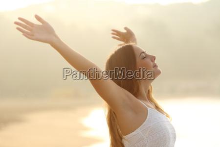 relaxed woman breathing fresh air raising