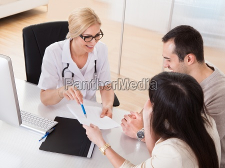 happy doctor discussing with couple