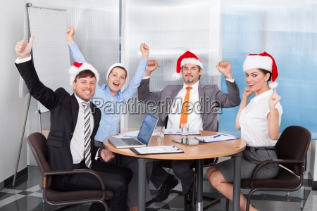 happy colleagues in santa hat celebrating