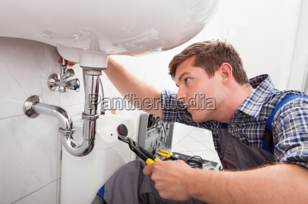 young plumber fixing a sink in