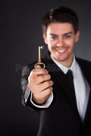 smiling businessman holding a golden key