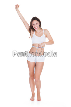 excited woman measuring her waist