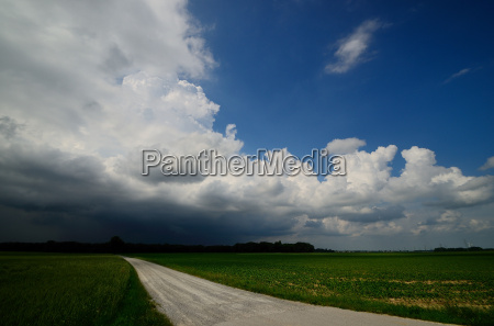 field path with black clouds