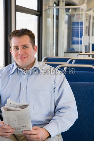 man on train with newspaper