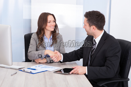 looking at businessman while shaking hand
