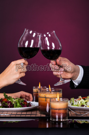 couple tossing wine glass