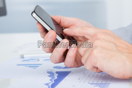 persons hand using cellphone above document